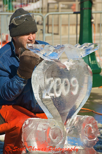 Ice carver Adam Vural puts the finishing touches to a Valentines Day themed sculpture.