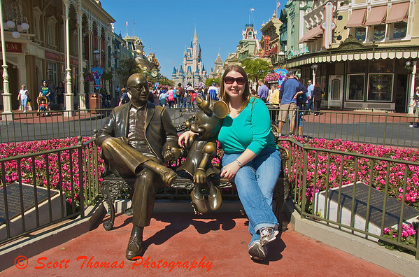 Sitting with Roy Disney.  My daughter sits with Walt Disneys brother and Minnie Mouse in the Magic Kingdom, Walt Disney World, Orlando, Florida.