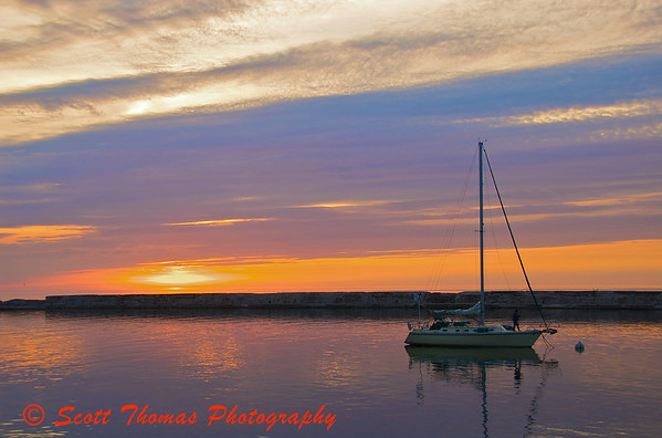 Sailboat anchored behind the Oswego Harbor breakwall for the night as the sun sets.