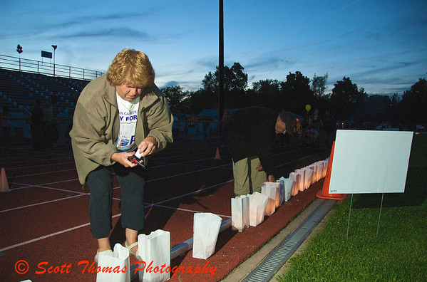 Volunteers help light the luminaries as darkness falls over the Baldwinsville, New York, Relay for Life Cancer fund raiser at the Pelcher-Arcaro Stadium on Friday, June 19, 2009.