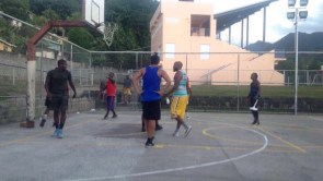 Kevin Wang (center, in blue), playing basketball with the locals at the community park in Gouyave.