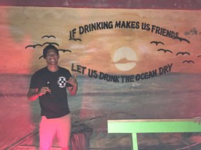 Kevin Wang poses in front of the mural at BG's Bar in Grenville.
