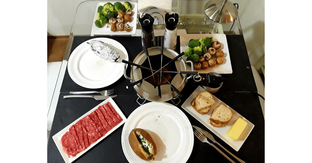 Fondue pot with fondue forks surrounded by two white round plates with backed potatoes, two white square plates with broccoli and mushrooms, and two white rectangular plates with thinly sliced meat and sliced sourdough bread and butter on a table with black placemats