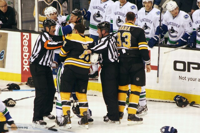 Referee Don Van Massenhoven breaks up a scrum between the Canucks and Bruins