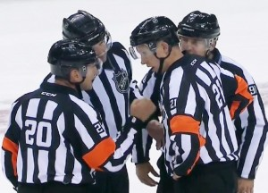 Referees Peel and Luxmore discuss the play with linesmen McElman and Mach
