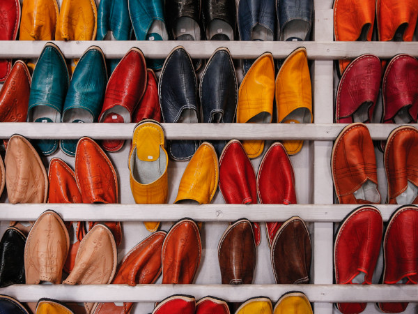 Display of lots of multi-colored shoes on white shelves
