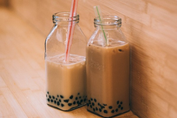 Two clear glass jars filled with bubble tea
