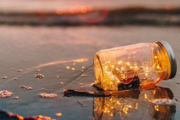 Gold mason jar on the beach at sunset