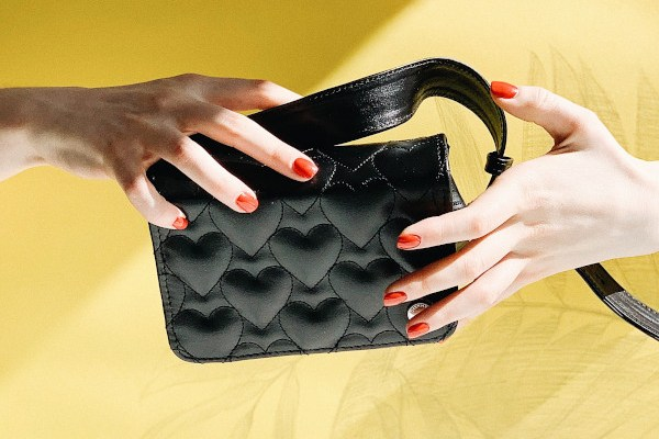 Two hands exchanging a purse in front of a yellow background