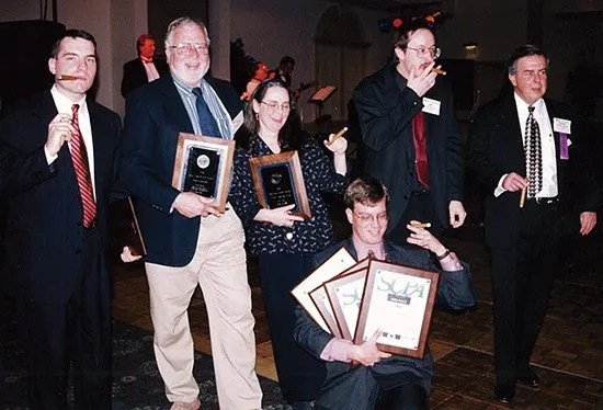 """Hubert Osteen, Jr. (far right) celebrates winning numerous awards while enjoying the traditional """"celebratory cigar"""" at one of the SCPA meetings."""