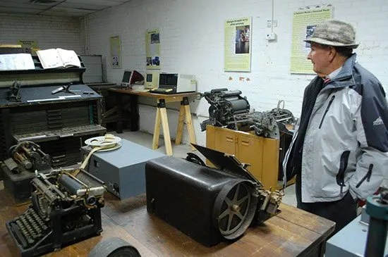 Bill Kinney surveys the Bennettesville Printing Museum created by his grandson as an Eagle Scout project.