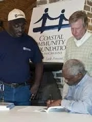 """Frazier signs a copy of his book """"Behind God's Back."""" Photo Credit: Post and Courier"""