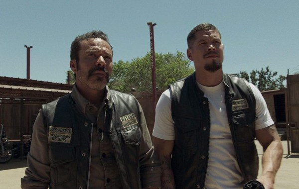two people, motorcyles in background, goatee, mustache