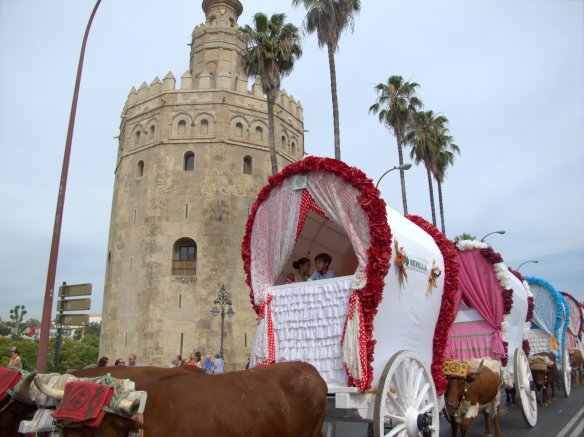 Carrozas passing the Moorish Torre del Oro, by the river.