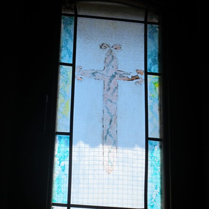 Stained glass window in the chapel showing the Cross of Santiago.