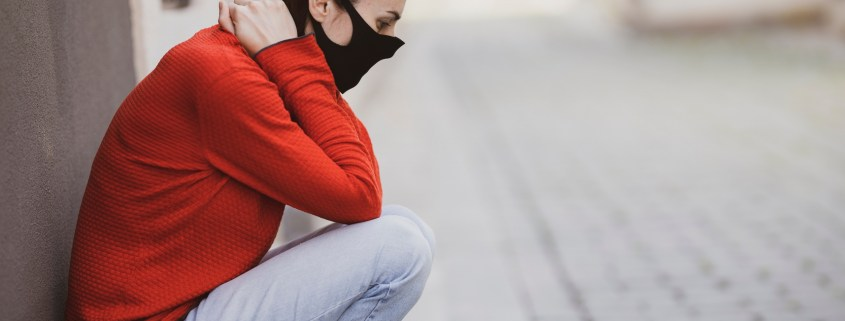 Image of a distressed person with a face mask on