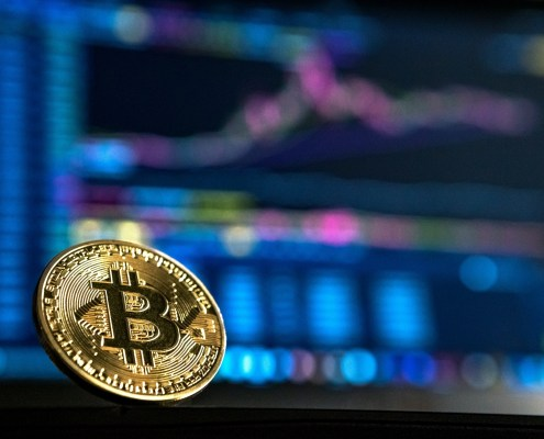 Image shows the crypto market with charts in the background