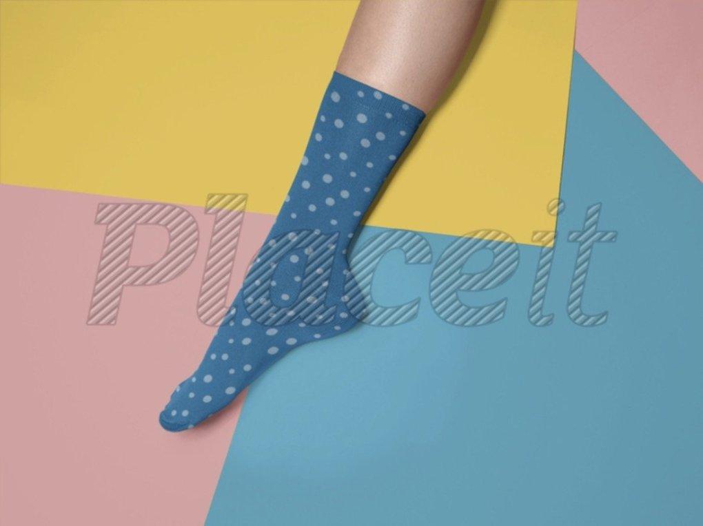 maquette d'une jambe allongée portant une chaussette tout contre une surface tricolore