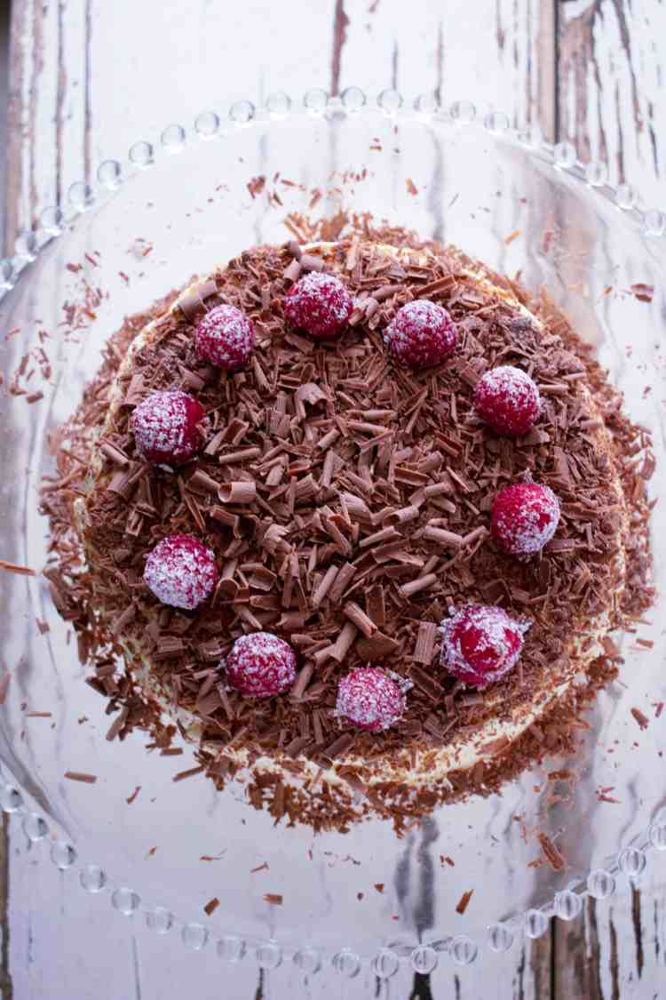 A top down view of a chocolate ripple cake with chocolate shavings and fresh raspberries.