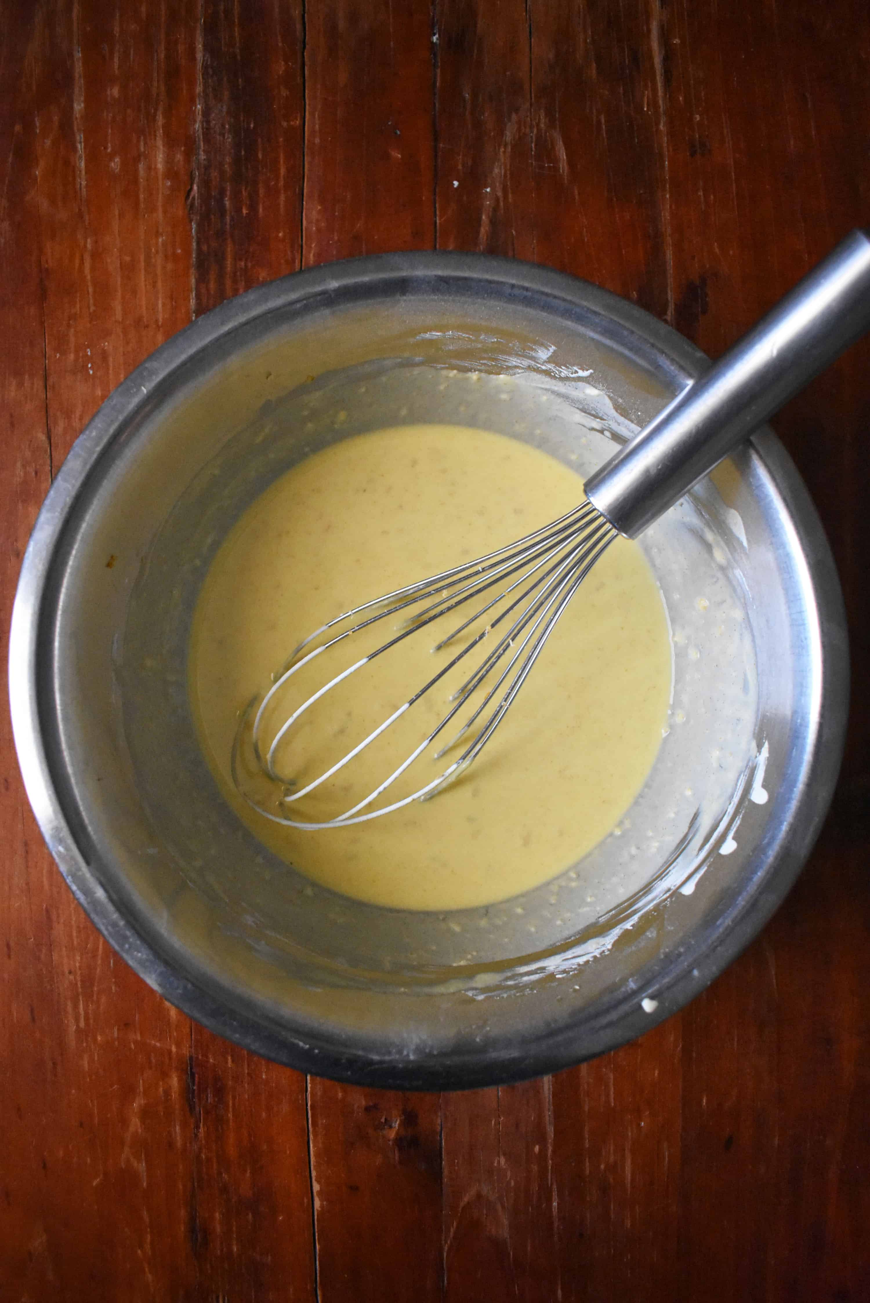 Whisking batter in a large mixing bowl.