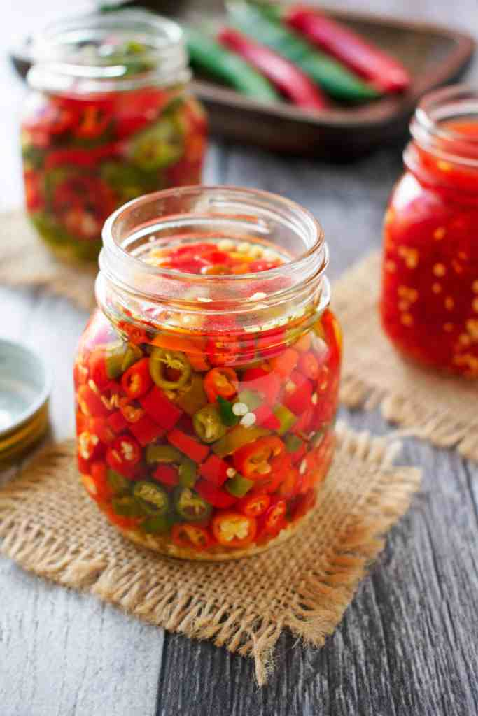 Three glass jars of different types of pickled chillies.