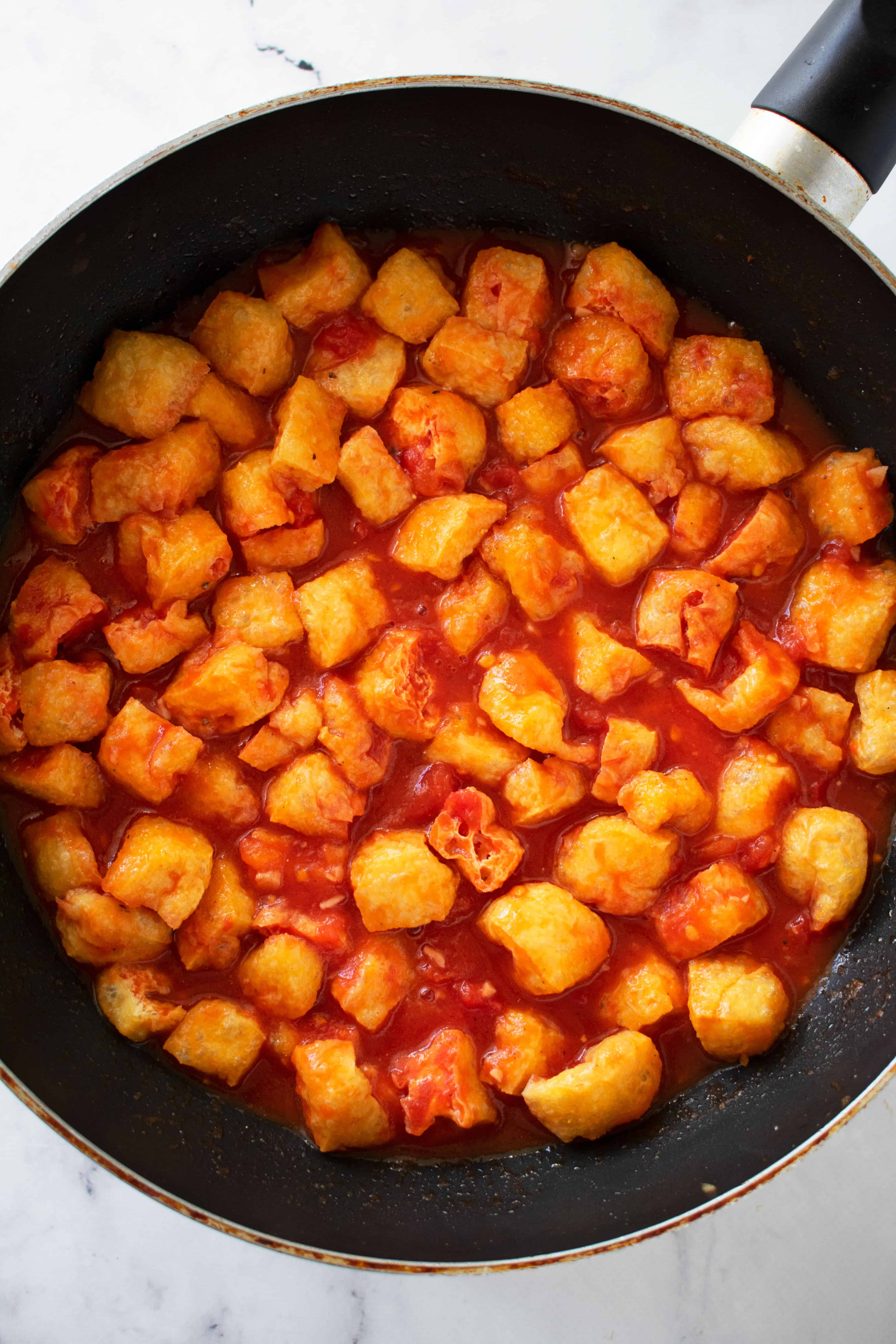 Tofu puffs drenched in red tomato sauce in a black fry pan