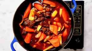 A recipe progress photo showing a dutch oven containing bo kho, right after adding carrots and onion