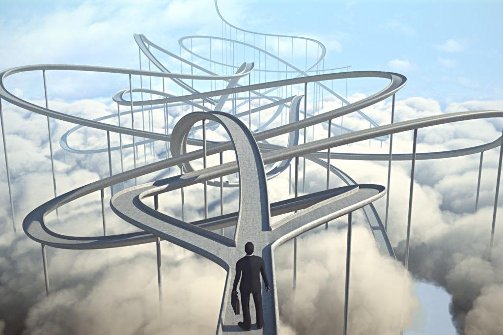 businessman looks ahead at winding paths