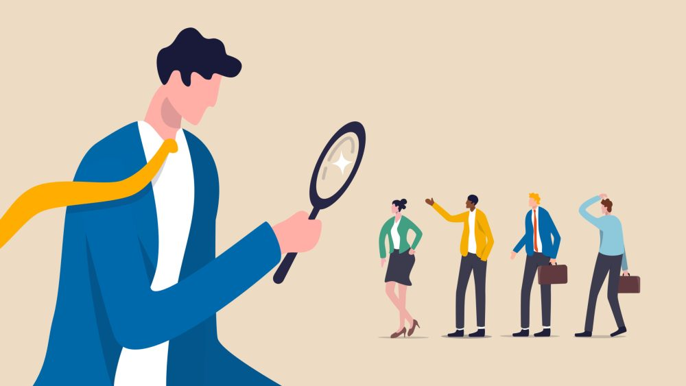 hiring manager searches for job candidates with magnifying glass