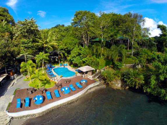 An aerial view of Lembeh Resort shows off the pool area; bungalows are tucked into the hillside at the right. The restaurant and reception area, behind the pool, are completely obscured by the lush vegetation.