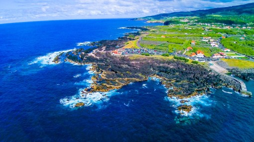 The dramatic coastline of Terceira is dotted with farms and tidy red-roofed villages. (Photo credit: Kenzo Kiren)