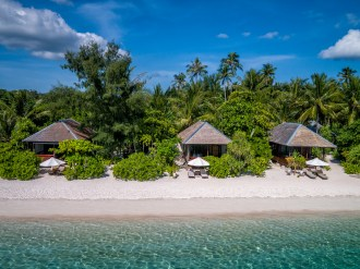 Ocean bungalows sit right on the bright white sand of Wakatobi Dive Resort, just steps from the welcoming water. Photo credit: Didi Lotze