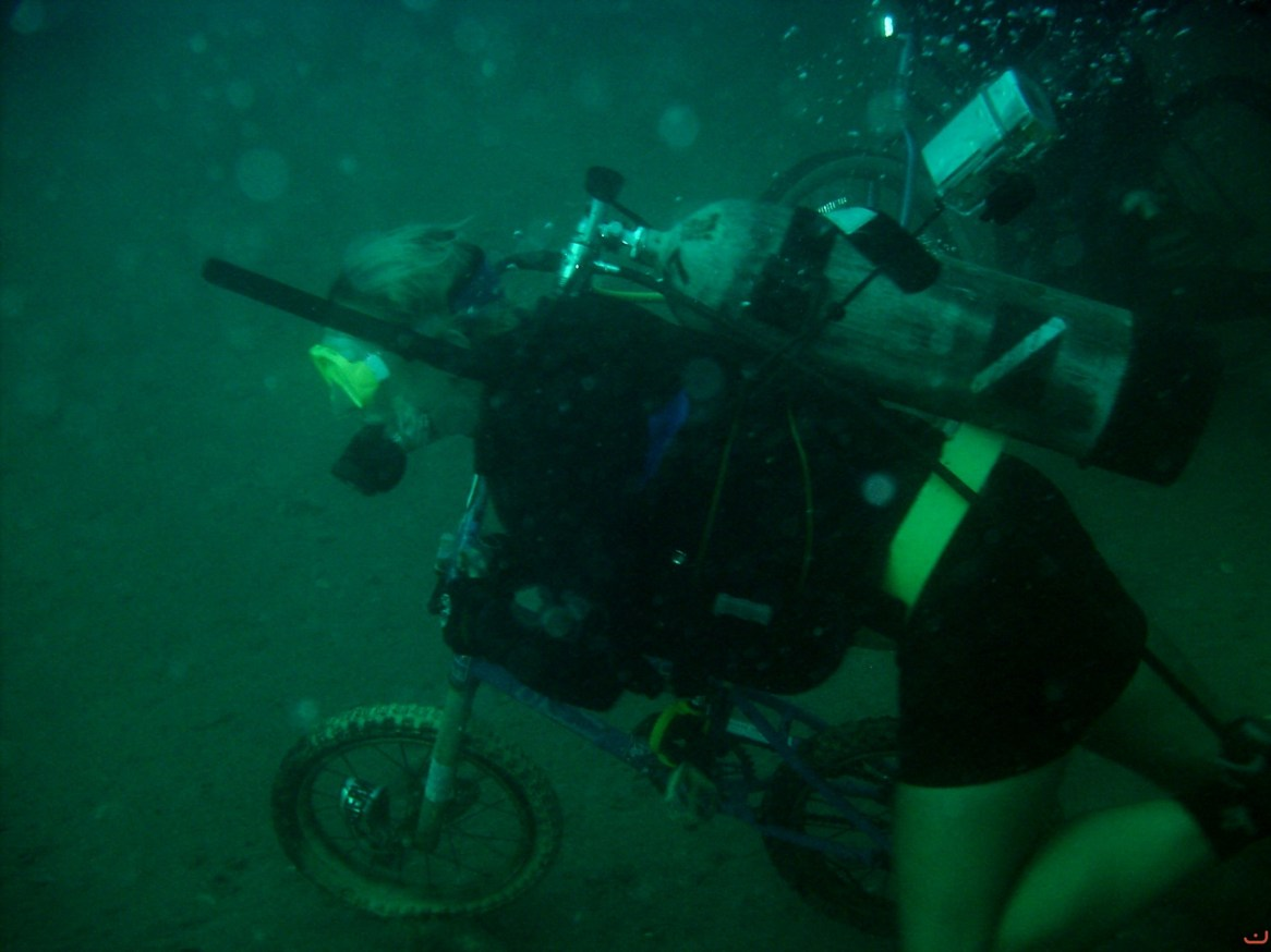 Racing a child-sized bike next to the USS Indra wreck. Photo courtesy of Discovery Diving.