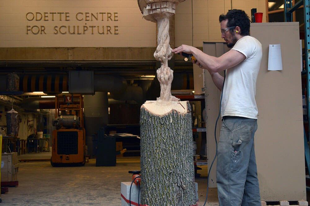 Sculptor Maskull Lasserre carving Schrodinger's Wood