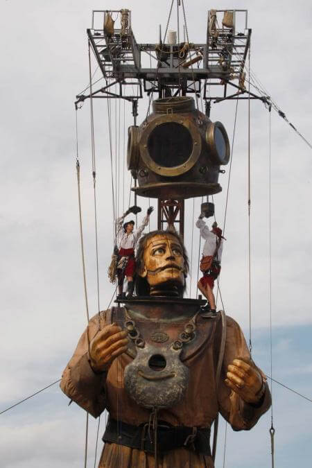 Giant sculpture puppet watches as he is helped with his helmet