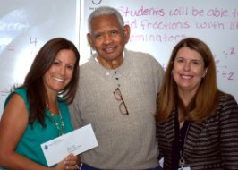 """Ed """"Papa Duck"""" Bolden (center) presents a check for a $200 classroom grant to James Foster Elementary School teacher Shauna Booth (left) with principal Dr. Deborah Bohn in attendance. Mrs. Booth was the winning teacher in Samuel Dixon Family Health Centers' annual rubber ducky school essay/poster contest."""