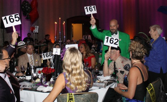 "Guests at the ""Clue"" table raise their bidding paddles to support the ""Buy a Bus"" campaign."