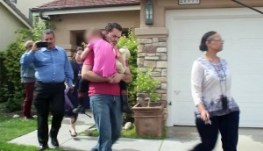 Foster parent, Rusty Page, and DCFS social workers bring Lexi out of the foster home in Saugus Monday afternoon for relocation.
