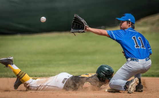 Canyon High School's Conrad Meza dives back to second base during a pick-off attempt as Northridge Academy's Kenny Le (11) awaits the throw. Meza was safe on the play. Photo: Kevin Karzin.