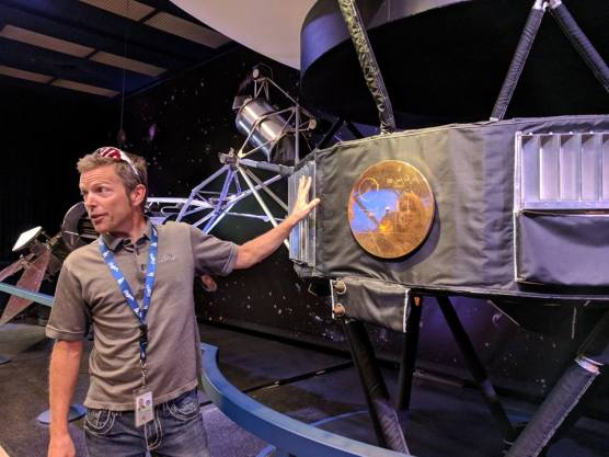 """Scott Evans at JPL in Pasadena (actually La Canada) talks about the Voyager missions in front of a life-size model of the Voyager spacecraft including the famous """"gold record"""" sent as a message from Earth to whomever might one day come across the ship."""