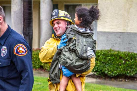 A firefighter carries a child to an ambulance after first responders worked to keep her from falling through a second-floor window on the 26700 block of Isabella Parkway in Canyon Country. The child was apparently left home alone. | Photo: Austin Dave/The Signal.