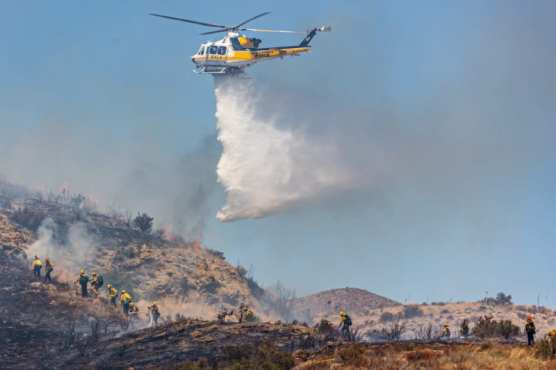 Los Angeles County Fire copter 14 makes a drop as Los Angeles County firefighters and Angeles National Forest firefighters work to douse the Dulce Fire off of the southbound interstate 5 freeway in Agua Dulce Sunday afternoon. | Photo: Cory Rubin/The Signal.