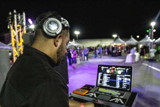 "An SOS Entertainment DJ plays music for crowds at ""Cocktails on the Roof,"" September 6, 2019. 