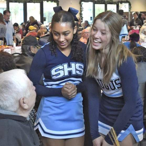 first Thanksgiving - Saugus High School cheerleaders Mikayla Pinantanida, left, and Faith Emard chat with attendees during the Senior Center Thanksgiving Gourmet Feast and Party held at the Bella Vida, Santa Clarita Valley Senior Center on Thursday, November 28, 2019. | Photo: Dan Watson / The Signal.