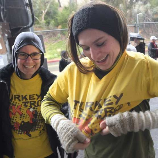 Participants Brittany Burkhead, left, and Emily Brumleve put on their t-shirts as they prepare for the start of the 11th annual Thanks Giving Day Turkey Trot event held at College of the Canyons on Thursday, November 28, 2019. | Photo: Dan Watson / The Signal.