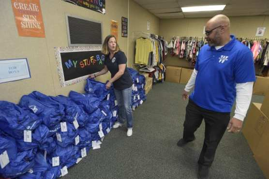 """District Coordinator of Special Programs Sarah Johnson, left, and Principal Tim Lankford discuss the """"stuff bags"""" and clothing available at the Wiley Canyon Elementary School Family Resource Center in Newhall on Thursday, November 21, 2019. 