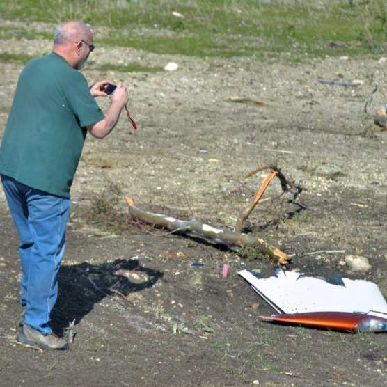 Federal Aviation Administration Aviation Safety Inspector Brian Ashton takes photographs of a tree limb and a piece of the wreckage from a small plane that crashed near the 14 Freeway and Newhall Avenue in Newhall on Saturday, January 4, 2020.   Photo: Dan Watson / The Signal.