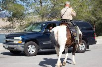 Deputy Fred Gonazalez greets two people in a car parked near the lake.