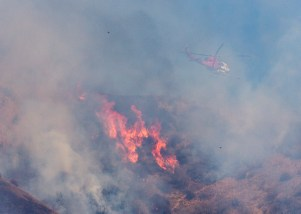 A helicopter flies over flames on a ridge near Greensbrier Drive.