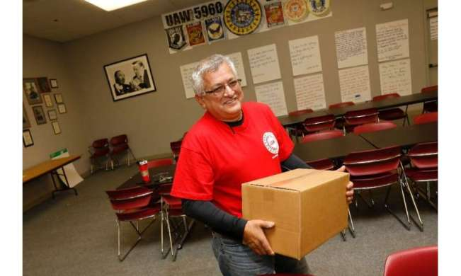 Louis Rocha, president of the UAW Local 5960, carries a box of food supplies for a striking worker on October 11 in Lake Orion,